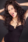 Aggressive sexy woman with long curly hair — Stock Photo