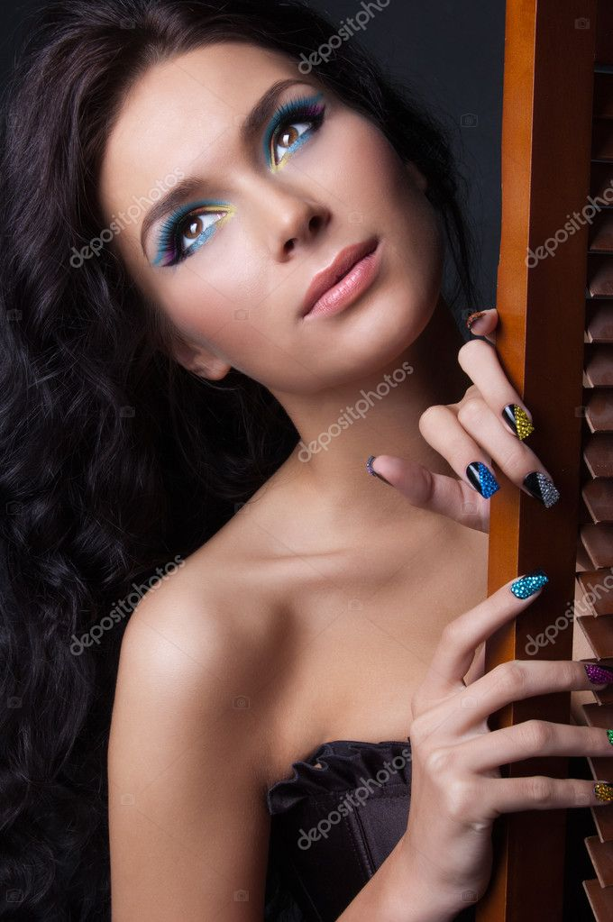 Woman with professional colourful make-up and sparkling manicure isolated on black — Stock Photo #6085101