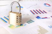 Padlock and financial graphs — Stock Photo