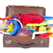 Open suitcase full of summer vacation or holiday things — Stock Photo