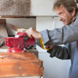 Old elderly man sawing in workshop shed — Stok fotoğraf