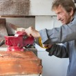 Old elderly man sawing in workshop shed — Stock Photo #6047788