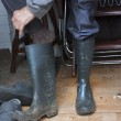 Man putting old welly boots on — Stock Photo