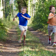 Young children running in nature - Stock Photo