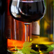 Bottle of red wine with glassand leaves. — Stock Photo