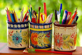Three jars, pencils and school objects on a green background — Stock Photo