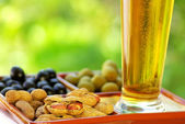 Beer glass with peanuts and olives — Stock Photo