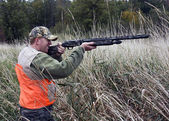 Hunter in marsh grass — Stock Photo
