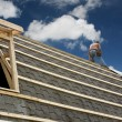 Carpenter roofing a barn - Stock Photo