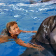 Child and dolphin in blue water. - Stock Photo