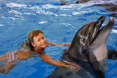 Child and dolphin in blue water. — Foto de Stock