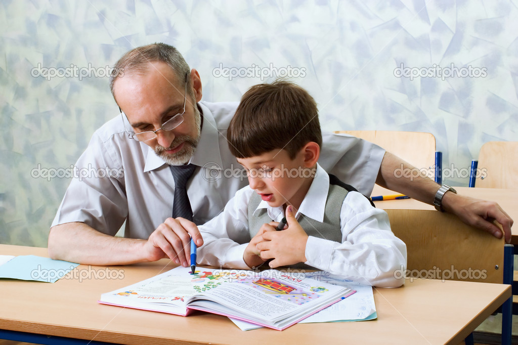 Primary school. The teacher learns the boy to read  Stock Photo #6318389
