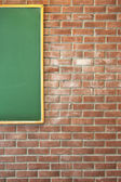 Red brick wall with a green blackboard — Stock Photo