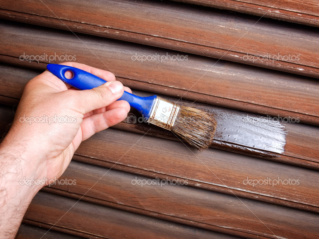Maintaining  of wooden surfaces with fresh protective paint... — Stock Photo #5702262