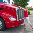 Pretty blonde woman opening a truck hood. — Stock Photo