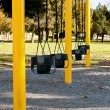 Swings for toddlers at a city park - Stock Photo