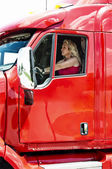Pretty blonde woman driving a big truck — Stock Photo