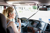 Blonde woman truck driver talking on her radio. — Stock Photo