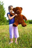 Girl with teddy bear in a meadow — Stock Photo