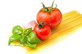 Raw spaghetti with tomatoes — Stock Photo