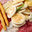 Platter of cured meats, cheeses and fried dumpling — Stock Photo #6124859