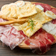 Platter of cured meats, cheeses and fried dumpling — Stock Photo #6124937