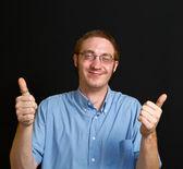 Lachende jongeman met duimschroef opwaarts — Stockfoto