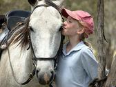Girl kissing horse — Stock Photo