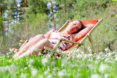 Young woman lying in a deck chair — Stock Photo