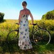Attractive young woman with a bicycle pauses at the edge of a rapeseed field — Stock Photo