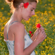 Young beautiful woman picking red poppies in a field of rape — Stock Photo