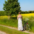Royalty-Free Stock Photo: Attractive young woman with a bicycle pauses at the edge of a rapeseed field