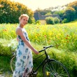 Attractive young woman with a bicycle pauses at the edge of a rapeseed field — Foto Stock