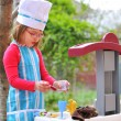 Stock Photo: Little girl having fun playing cooking