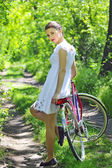 Young girl with a vintage bicycle — Stock Photo