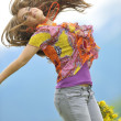 Beautiful woman jump on field — Stock Photo
