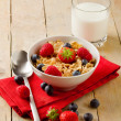Corn flakes with berries on wooden table - Stockfoto