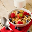 Corn flakes with berries on wooden table - 图库照片