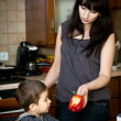 Stock Photo: Mother offers red Bulgarian pepper to her child
