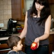 Mother offers red Bulgarian pepper to her child — Stock Photo #5415251