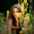 Portrait of a young woman on flowers field — Stockfoto