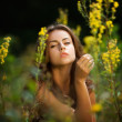 Portrait of a young woman on flowers field — Stock Photo