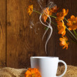 Cup of coffee with orange flowers - Stockfoto
