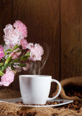 Cup and coffee beans and flowers — Stock Photo