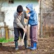 Stock Photo: Senior farmer with grandson in the garden