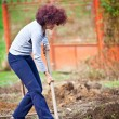 Redhead young lady digging in the garden — Stock Photo #5473309
