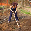 Young woman digging into the garden — Stock Photo
