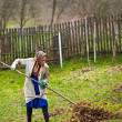 Senior farmer spring cleaning the garden with a rake — Stock Photo