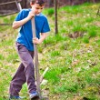 Farm boy digging with a shovel — Stock Photo
