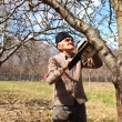 Old farmer trimming apple trees — Stockfoto